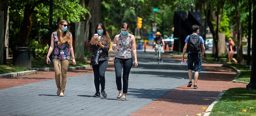 a photo of three people walking across the Penn campus with masks on