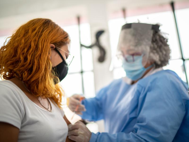 A person being vaccinated against COVID-19 by a gowned and masked woman.